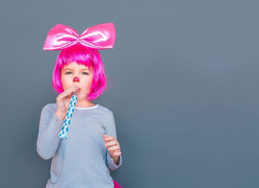 Caucasian girl with pink wig and ribbon blowing a party horn