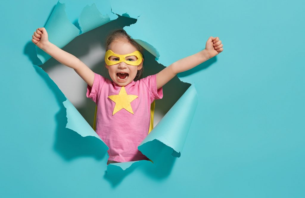 Girl in superhero costume bursting out from a paper wall