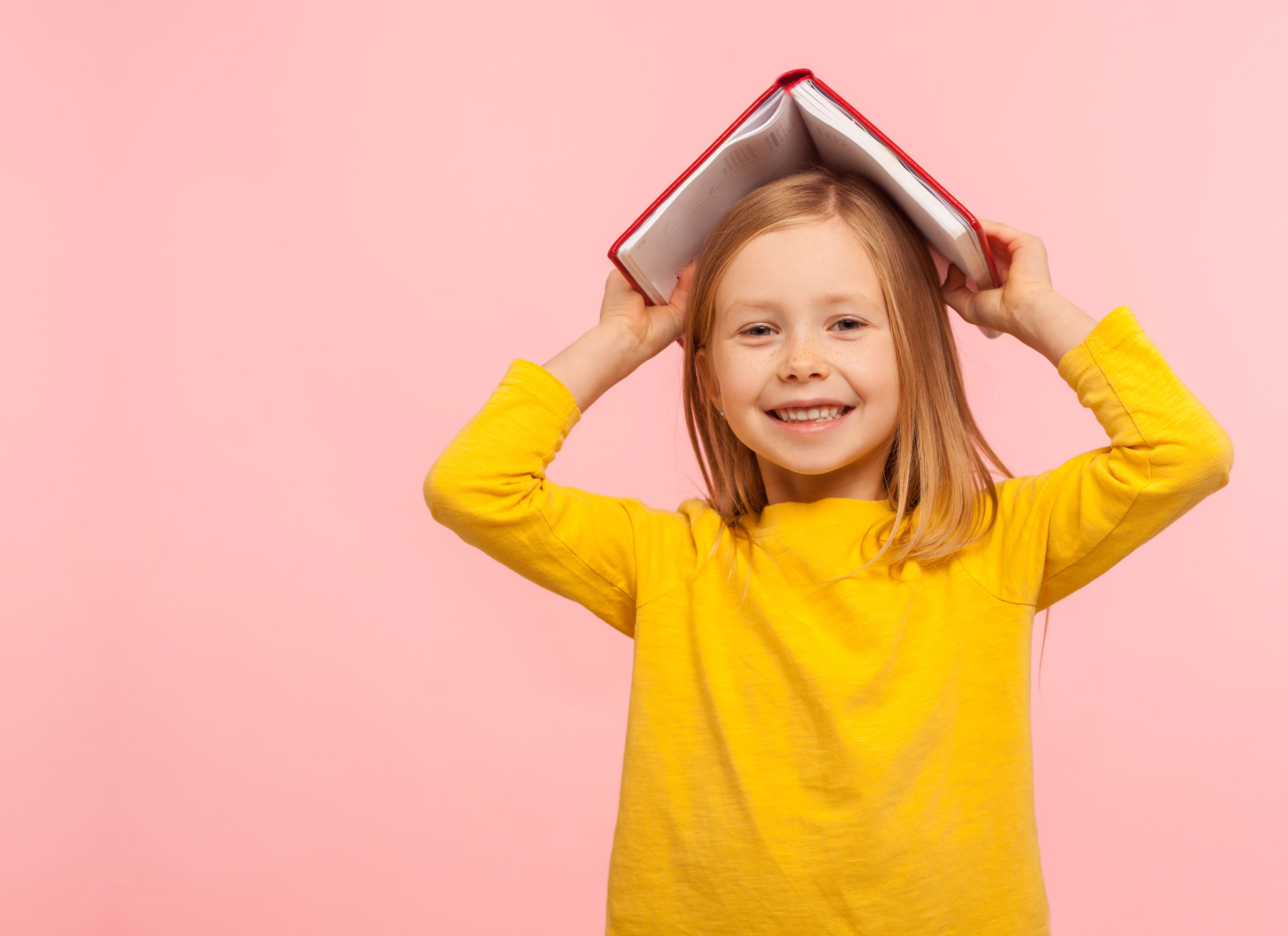Smiling Caucasian girl in yellow top with hardcover book on her head