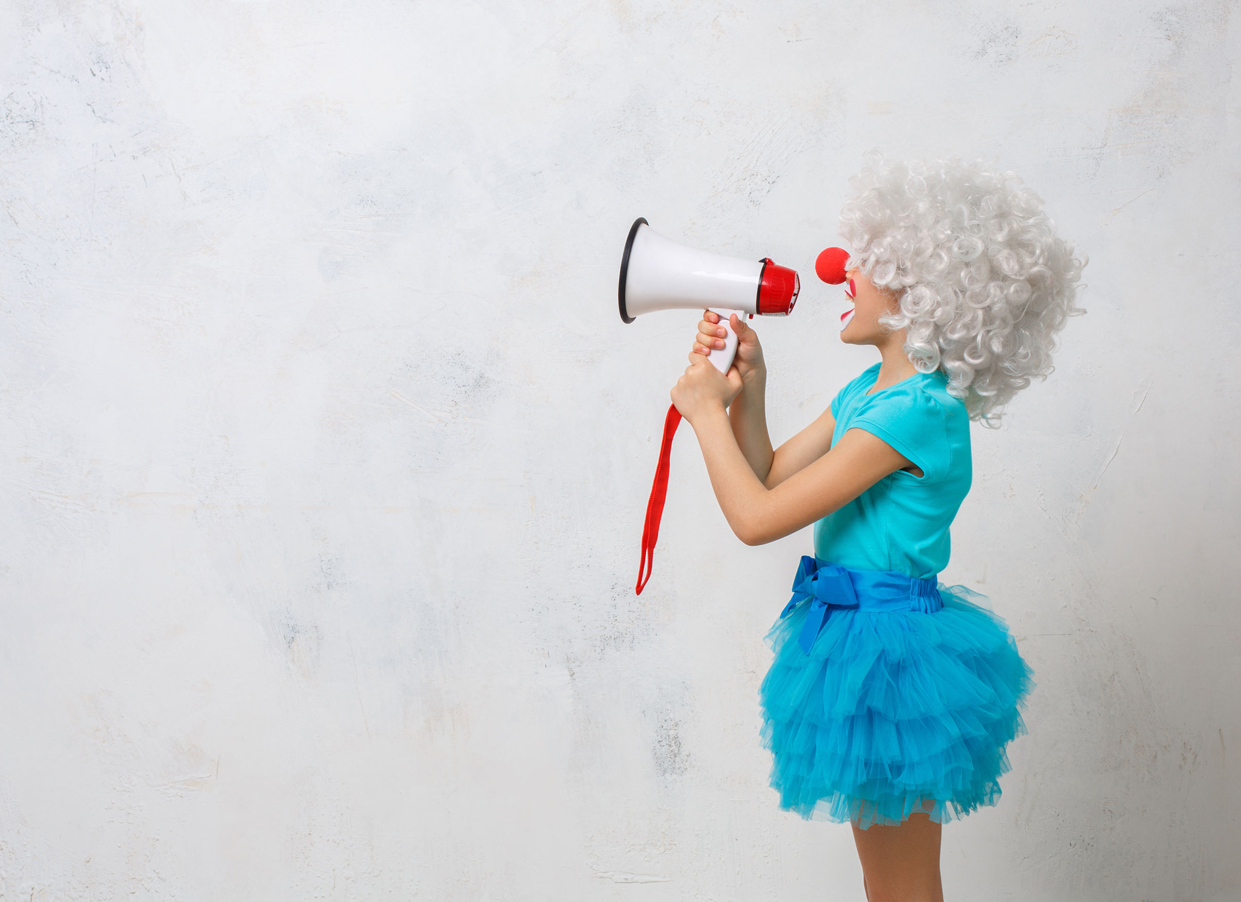 Side view of child in grey wig and cyan outfit speaking into a megaphone